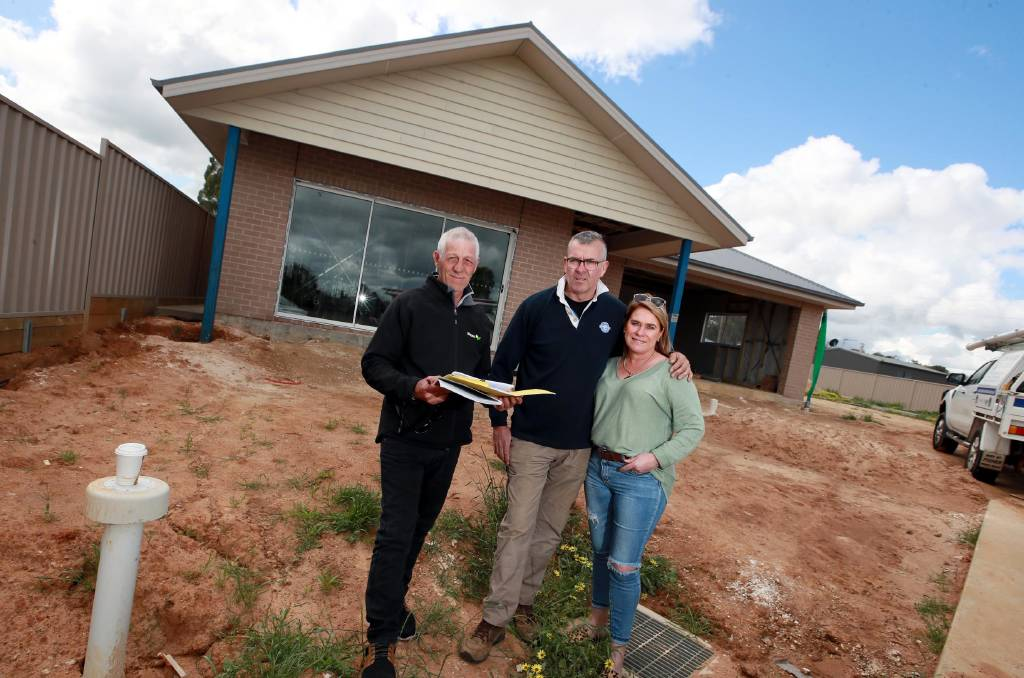 Andrew White with Geoff and Cathy Reid in front of the house that is starting to take shape in Boorooma. Photo: Les Smith